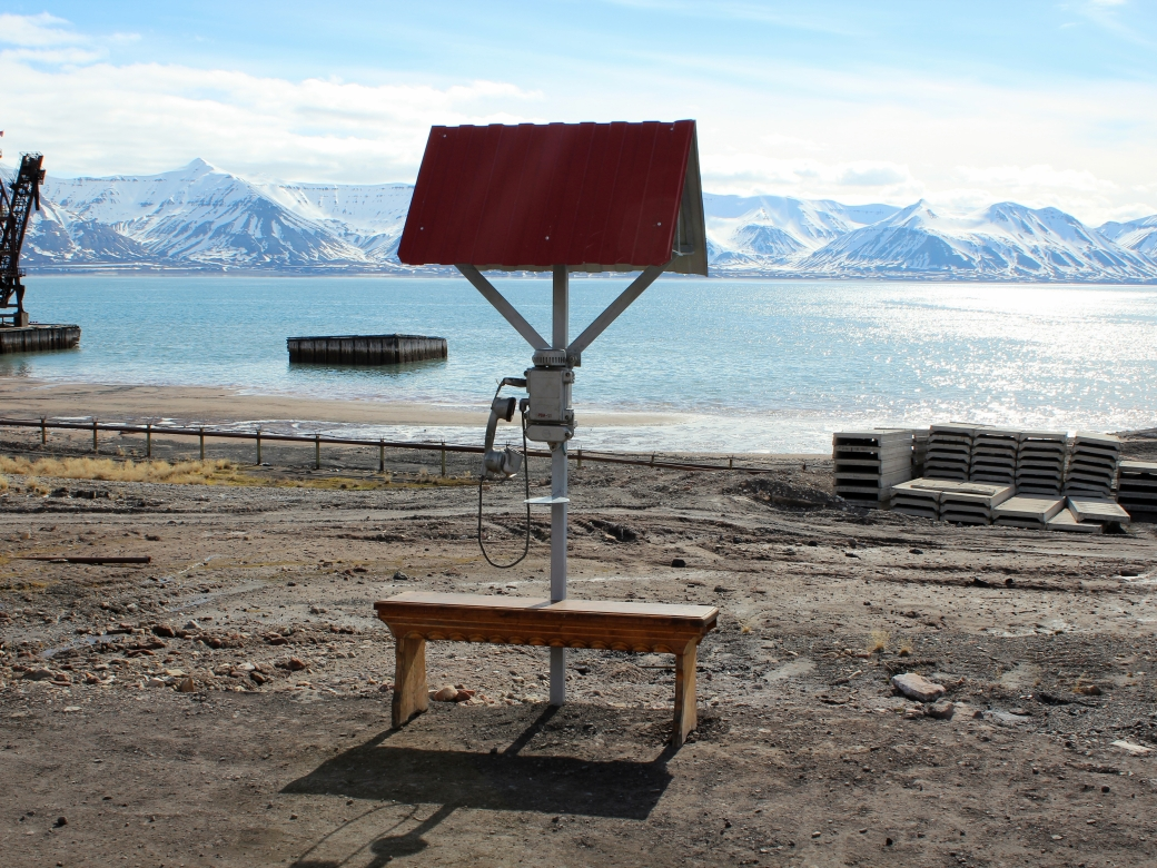 A telephone shelter and bench overlooking the sea and port. Pyramiden, Svalbard